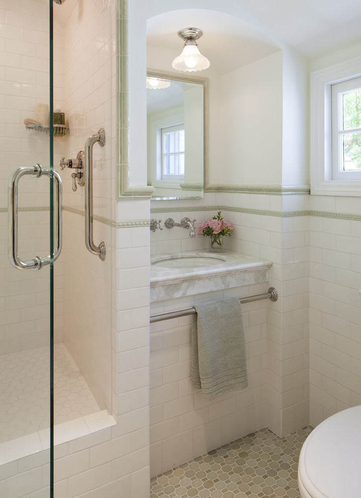 small marble sink with pedestal on white subway tiles with towel bar, mirror on top, small lights