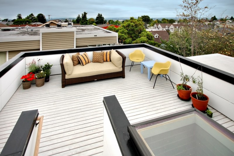 sofa and pillow throws in brown tone IKEA yellow chair light blue table white painted wooden rooftop deck clay pots