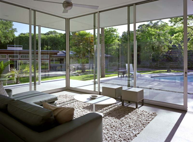 sunroom by the pool with white rug, grey corner sofa, white round wooden coffee table