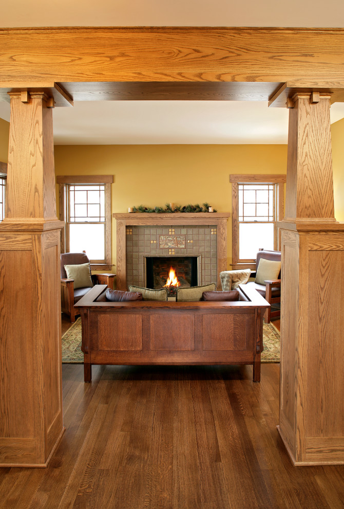 timeless living room idea in Mission style oak interior facade dark wood furniture tiled fireplace warm yellow walls dark toned wood floors