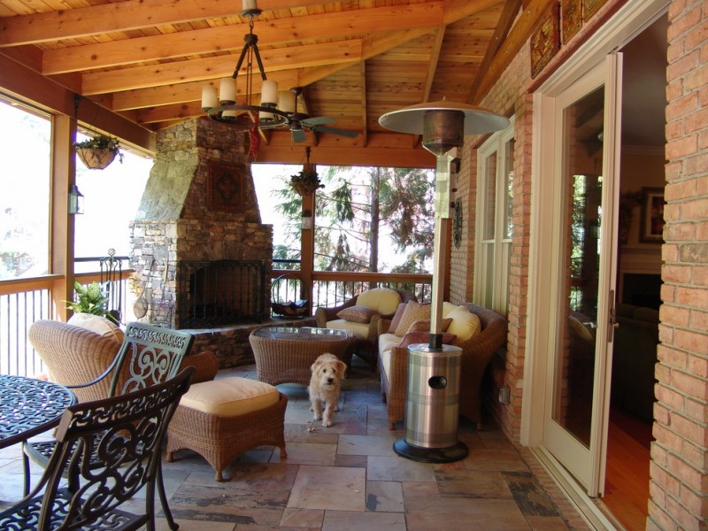 timeless porch with fire feature natural stone pavers chair sets sofa sets brick wall pendant lamp deck wooden ceiling