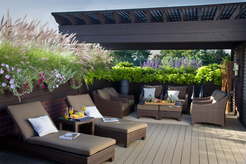 traditional deck with rattan lounges with brown cushion, rattan chairs with brown cushion, rattan table, plants pot along the rail fence