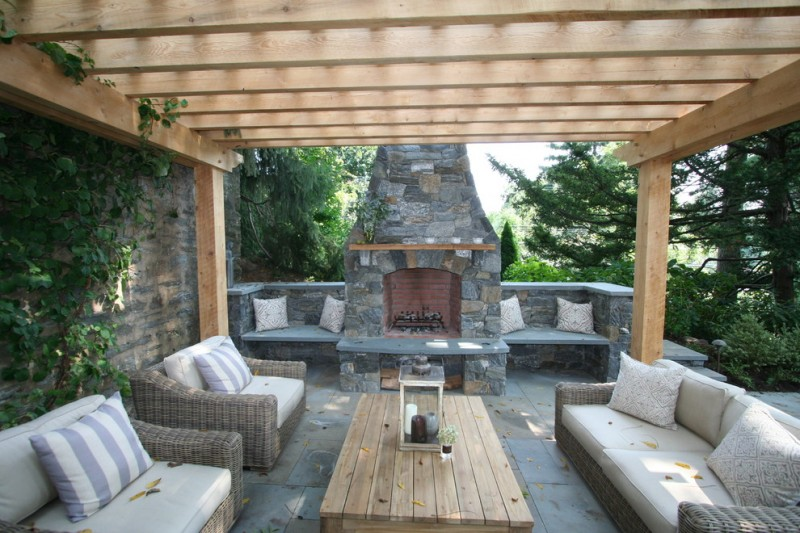 traditional patio with wooden pergola rattan furniture with white puffed comforters natural stone fireplace concrete pavers flooring idea