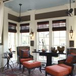 Traditional Sunroom With Red Rug, Rattan Lounge Chairs With Red Cushion, Round Top Side Table, Long Rectangle Wooden Table, Diamond Shaped Sconches