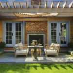 Transitional Patio Covered By Cedar Pergola Red Bricks Fire Feature Pale Toned Wood Furniture Concrete Slabs Floors