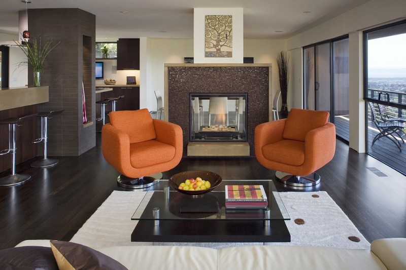 trendy living room design with a tile fireplace surround and brown floors orange swivel chairs glass and wooden coffe table medium toned wooden floors bar stool white carpet