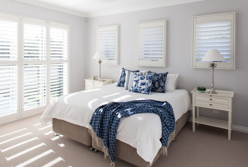 tropical bedding idea with blue accent linen and shams white bedside tables and table lamps light grey floors white walls accented by windows with white window shutters