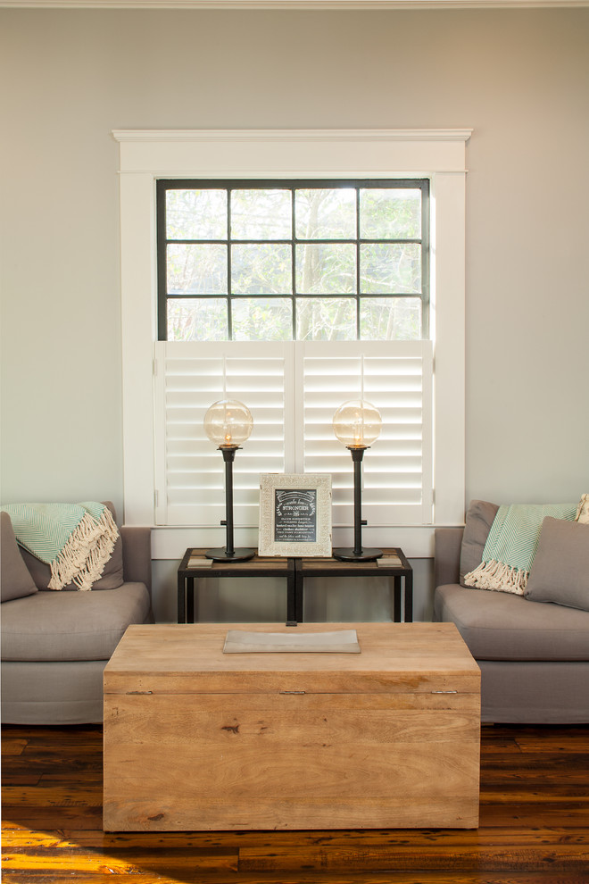 unfinished wooden center table grey walls modern grey couches with pillows and light turquoise blankets wood top side table with black wrought iron base dark hardwood floors