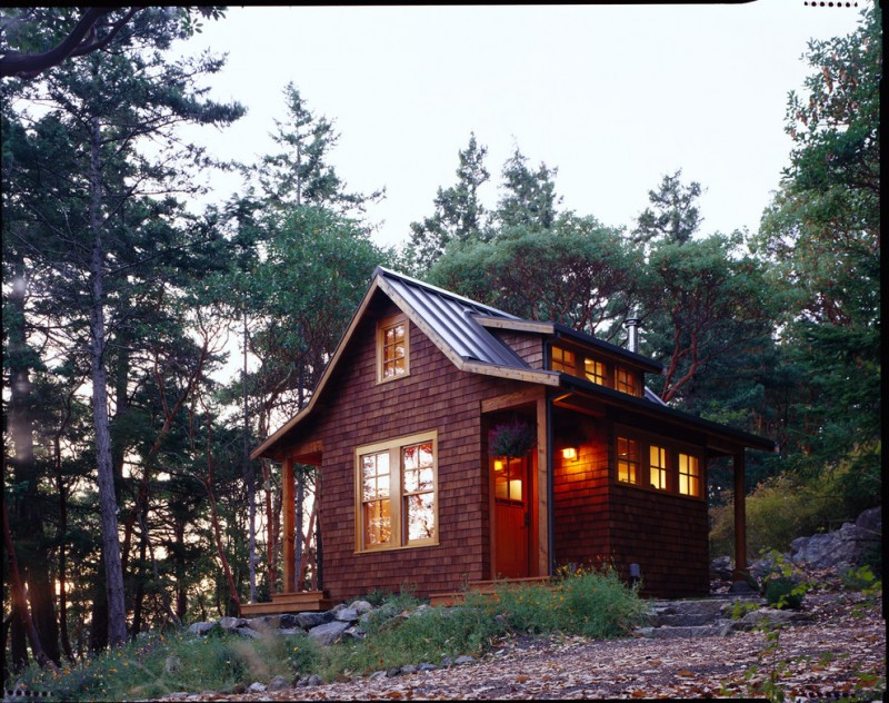 vacation home rustic exterior with patio wooden deck walls metal roof glasss windows lamps in yellow