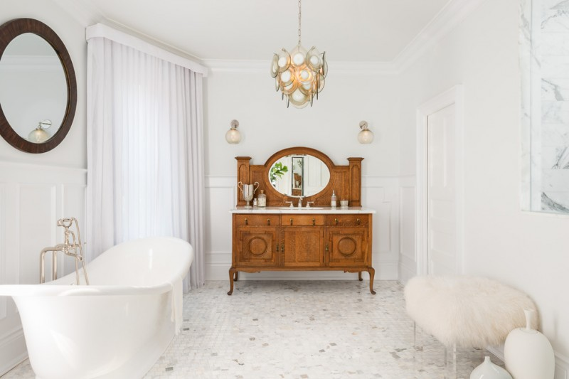 victorian bathroom with white mosaic tiles, white bath tub, white fur ottoman, brown wooden vintage vanity, glass sconces, beautiful chandelier