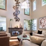 wall decorating ideas for living room artwork paintings trickling water couches armchairs sidetable fireplace carpet coffee table contemporary design