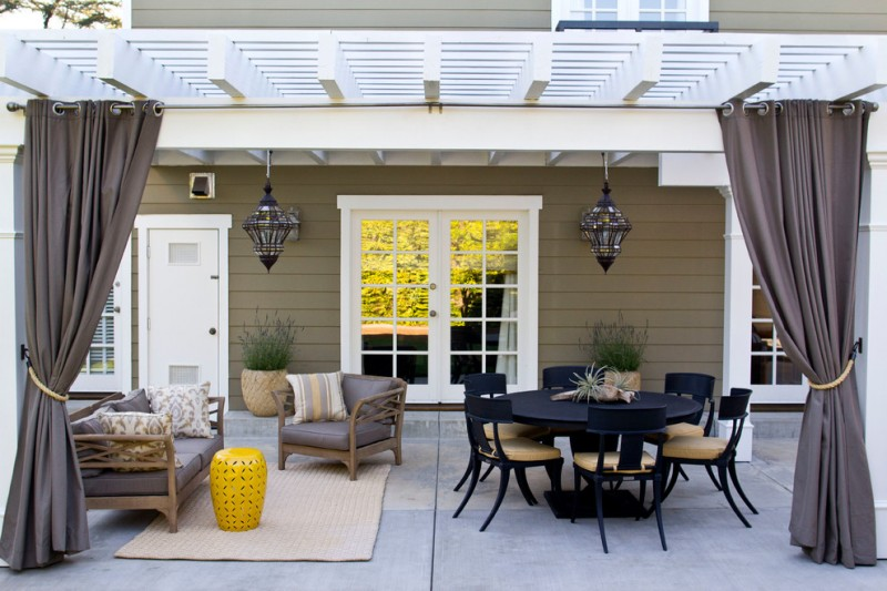 warm and modern patio white pergola with drapery solid black furniture set a couple of leather couches with pillows a couple of mosaic hang lamps