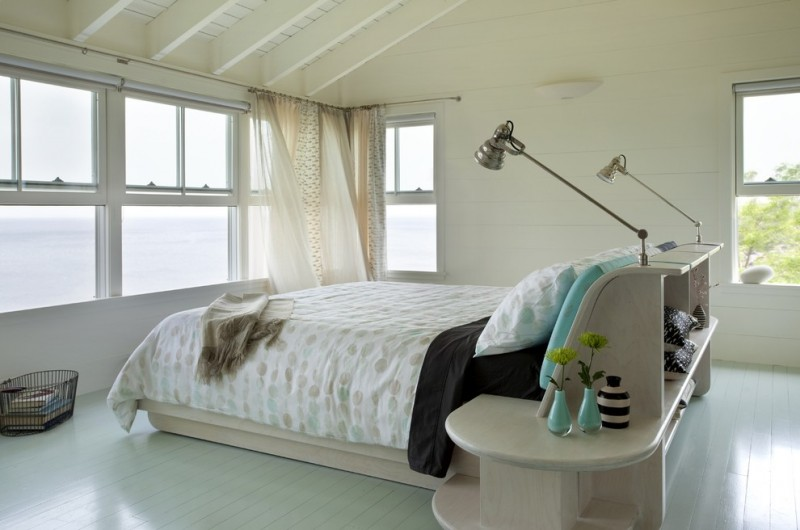 white duvet with light toned polka dots white bed frame with integrated bedside tables white painted wood floors white walls glass windows white wood ceilings with exposed beams