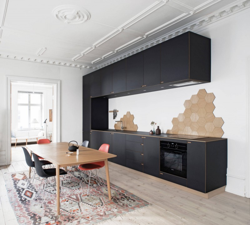 white wall black cabinet black appliances flat panel cabinet wooden table black bar stool red black stool light wood floor heptagon shaped wall feature area rug