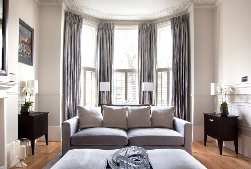 window treatment ideas for bay windows half shutters grey curtains grey couch grey ottoman dark brown wooden side table white wall large mirror fireplace white table lamps