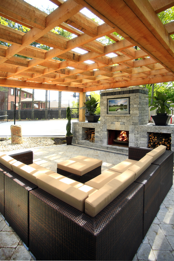 wooden pergola with thick wooden rafters L shaped modern couch with table bricks outdoor fireplace