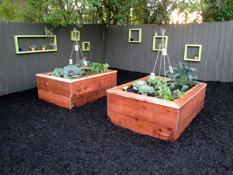 yard with vegetable planters, grey fence with neon green built in hangin frames