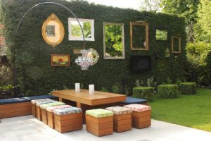 yard with wooden table, chairs with colorful cushion, mirrors and TV on the bush fence, lamps