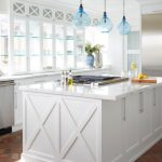 Coastal Kitchen Photo With Recessed Panel Cabinets, White Cabinets, Glass Cabinets, Stainless Steel Appliances, Brick Floors And An Island