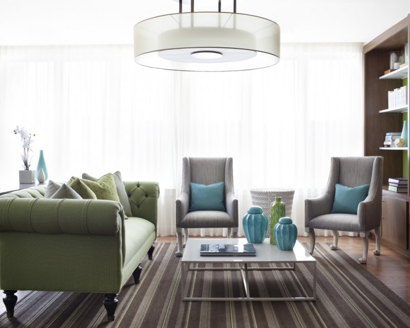 Contemporary living room with medium tone hardwood floors accent rug exposed chairs and table green sofa multicolor pillow throws window walls white curtains