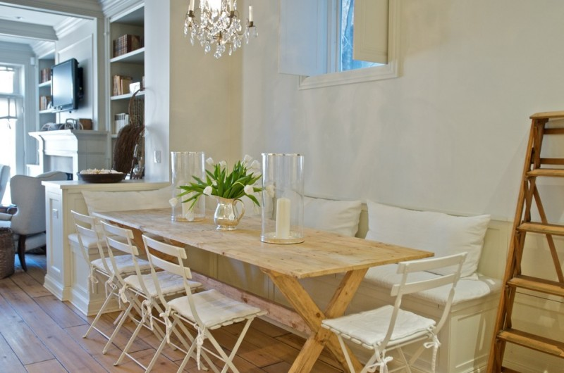 Elegant dining room with white walls and medium tone hardwood floors wooden chairs white painted benches seat chandelier lamp wooden stair