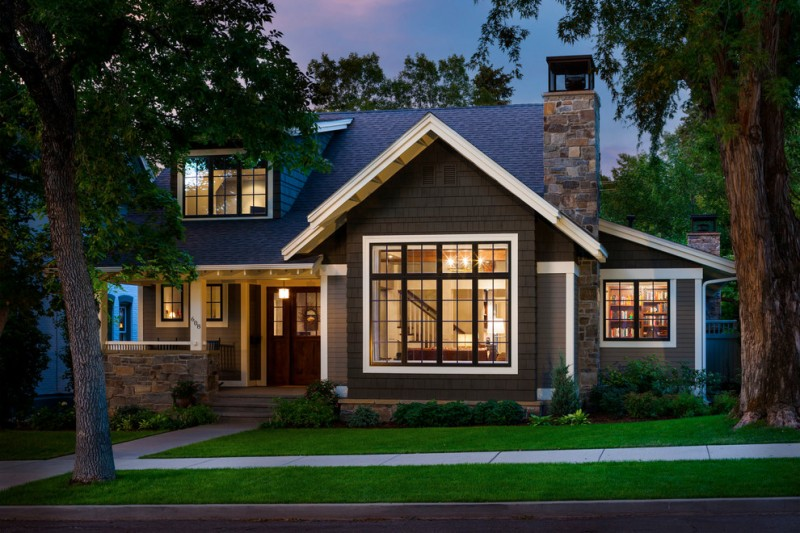 Elegant gray two story wood exterior home with a gable roof and vent pipe system dark painted aluminum clad wooden patio table sets
