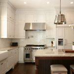 Elegant L Shaped Kitchen With A Farmhouse Sink, Paneled Appliances, Raised Panel Cabinets, White Cabinets, Marble Countertops, White Backsplash And Subway Tile Backsplash