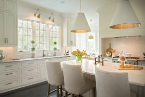 Timeless kitchen with dining table in white cabinet and countertop white chairs white cabinet floating cabinet white tile backsplash bronze pendant lights