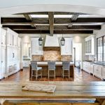 Traditional U Shaped Eat In Kitchen With Stainless Steel Appliances, Subway Tile Backsplash, A Farmhouse Sink, Soapstone Countertops, Shaker Cabinets, White Cabinets And White Backsplash