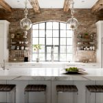 Transitional Galley Kitchen With A Farmhouse Sink, Recessed Panel Cabinets, White Cabinets And Paneled Appliances, Glass Pendant Lights Framed Glass Windows