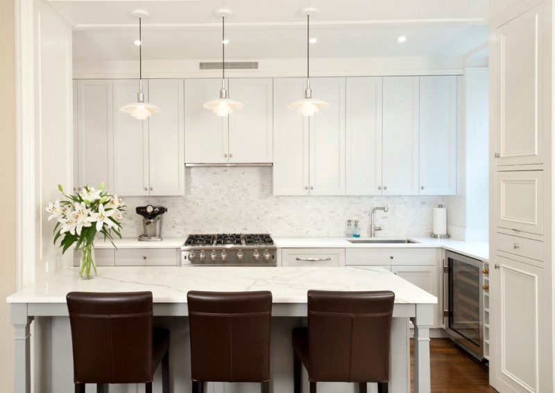 White kitchen cabinets and kitchen table floating cabinet white painted walls and door hanging lamp brown chairs light toned wooden floors