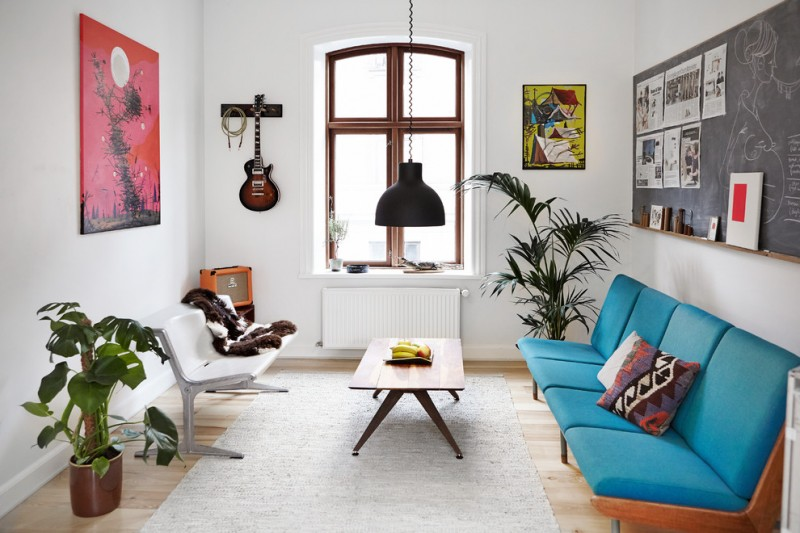 apartment living room ideas blue cuhshioned couch small rug plants decoration guitar holder bench wall decor industrial lamp in black window wood table