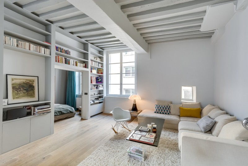 apartment living room ideas wood beam on ceiling corner beige couch wood with glass leg bar table fluffy rug white womb armchair built in shelving
