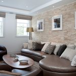 Asymmetrical Leather Couch With A Lot Of Pillows Black Leather Chairs Clean Lined Coffee Table Textured And Light Stone Walls