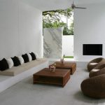 Beige Couch With Black White Accent Pillows A Pair Of Dark Toned Wood Center Tables With Decorative Planters Jute Bean Chairs White And Soft Concrete Walls White Concrete Floors