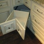 Bent Shaped Corner Cabinet In White With Raised Button Handles Made Of Metal