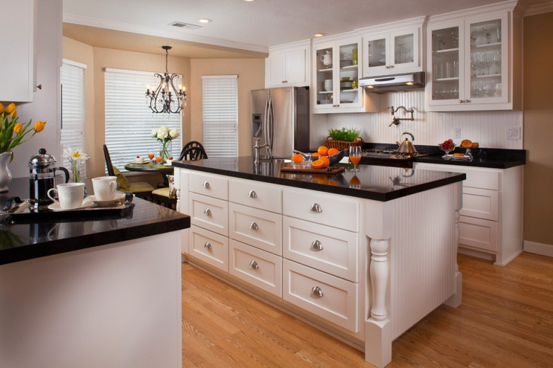 black and white kitchen white cabinet white kitchen island with black granite countertop wood flooring rustic faucet chandelier