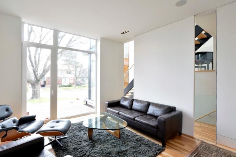 black leather lounge chair black leather Ottoman chair fluffy black area rug medium tone wood floors clean white walls