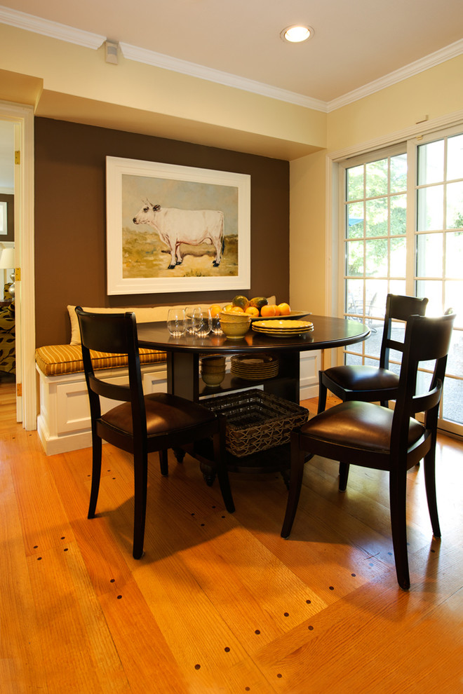 black round wooden table with shelves under, three black wooden chairs with black leather seating, white wooden bench with brown yellow striped cushion