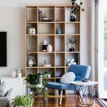 Blue Chair Round Wood Top Side Table Wood Shelving Unit Medium Toned Wood Floors