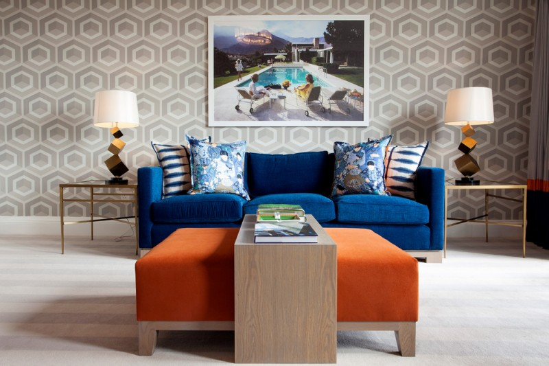 blue velvet couch with multicolored accent pillows wooden table on Ottoman table white floors modern patterned wallpaper a pair of simple side tables