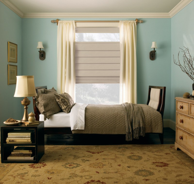 blue walls beige bedroom rug with floral motifs black finished bedside table dark finished bed frame with headboard wood dresser unit without finishing light cream draperies grey shades