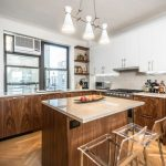 Brown Patterned Wooden Kitchen Island With Cream Marble Top And Clear Plastic Chairs