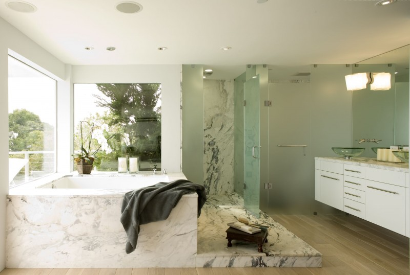 built in granite tub glass window tiled floor frosted glass door floating vanity glass sink recessed lights bathroom lights