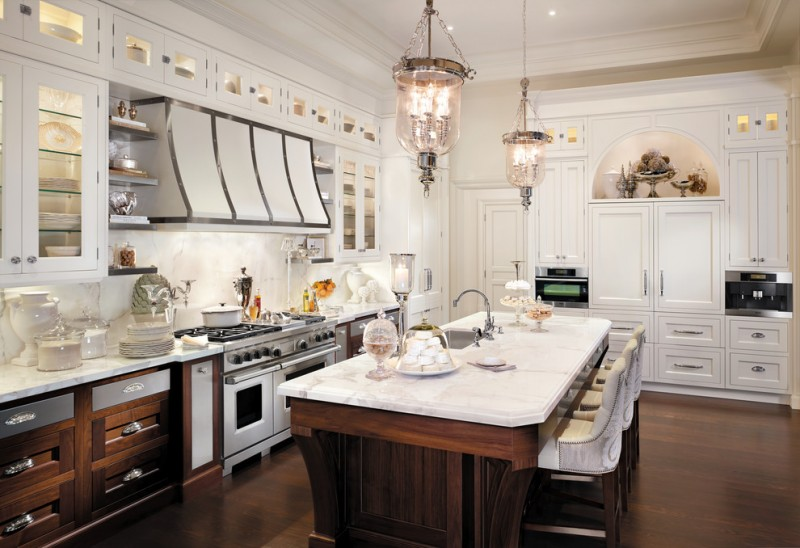 classic galley kitchen with recessed panel cabinets, white cabinets and white backsplash silver appliances medium toned wooden kitchen island and floors.