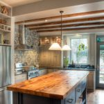 Classic L Shaped Kitchen With Raised Panel Cabinets, Wood Countertops, Blue Cabinets, Blue Backsplash And Stainless Steel Appliances Hanging Lamps Medium Toned Wooden Floors