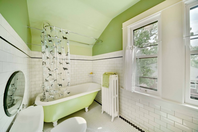 claw foot tub shower curtain towel holder rounded mirror octagon tiled floor tiled wall green ceiling glass window