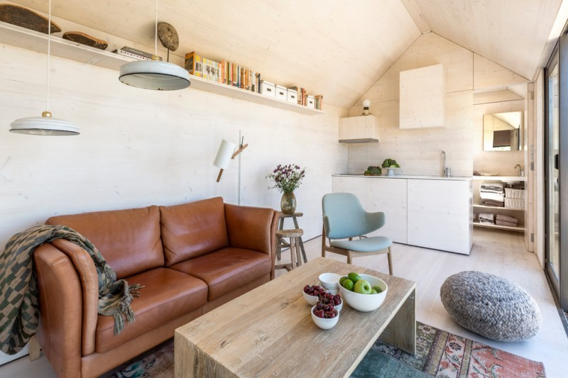 clean lines furniture set consisting of earthy brown leather couches light blue chair wool bean chair wooden center table without finishing tribal area rug whitewashed wood floors