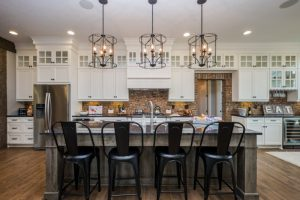 country galley kitchen with shaker cabinets, white cabinets, brick backsplash, stainless steel appliances, dark hardwood floors and wooden island granite countertop