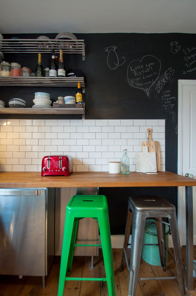 eclectic kitchen idea metal pipes shelving units chalkboard walls white subway tiles walls wood top dining table colorful plastic bar stools stainless steel appliances